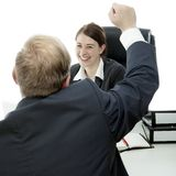 Business man woman at desk raise arms in the air. Beard business men brunette women at desk raise arms in the air and is happy Royalty Free Stock Images