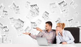 Business man and woman at desk with stock market newspapers Royalty Free Stock Images