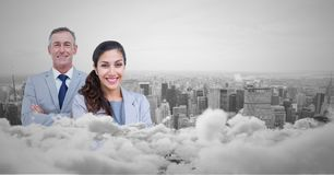 Business man and woman facing out with city skyline behind them and clouds in front. Digital composite of Business men and women facing out with city skyline Stock Image