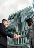Business man and woman handshake in front of the building. Digital composite of business men and women handshake in front of the building Royalty Free Stock Photos