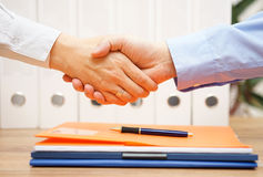 Business man and woman are handshaking over documents in with of. Fice in background stock image