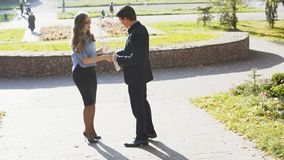 Business man and woman having meeting and conversation outdoor. 4k stock footage