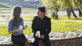 Business man and woman having meeting and conversation outdoor. Shot in 4k stock footage