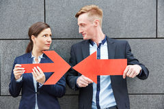 Business man and woman holding arrows against each other. Business men and women holding two big red arrows against each other Royalty Free Stock Images