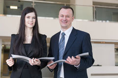 Business man and woman are holding magazines royalty free stock images