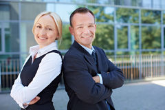 Business man and woman leaning back. Business men and smiling women leaning back on back outside the office Royalty Free Stock Images