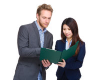 Business man and woman looking at clipboard Stock Images