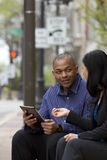 Business man and woman outside on their break with their tablets Stock Images