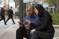 Business man and woman outside on their break with their tablets Stock Photo