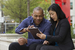Business man and woman outside on their break with their tablets Royalty Free Stock Image