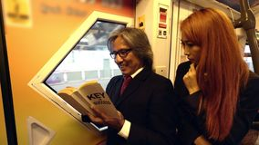 Business man and woman on the train station. Business man and woman are reading book on the train