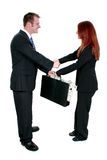 Business Man and Woman Shaking Hands Over Briefcase of Money Stock Photo