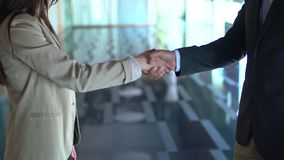 A business man and woman shaking hands. In slowmotion stock video