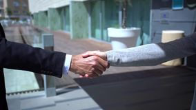 A business man and woman shaking hands. In slowmotion stock video footage