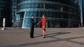 Business man and woman shaking hands. Young cheerful Business partners man and woman doing a handshake in suit outdoor. Glass modern office building district bg stock footage