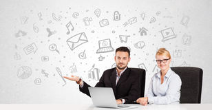 Business man and woman sitting at table with hand drawn media ic Stock Photography