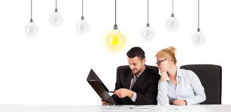 Business man and woman sitting at table with idea light bulbs Royalty Free Stock Photo