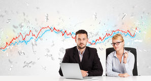 Business man and woman sitting at table with stock market graph Royalty Free Stock Images