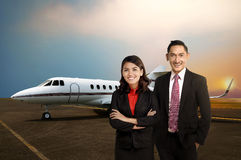 Business man and woman smiling in front of private jet Royalty Free Stock Photo