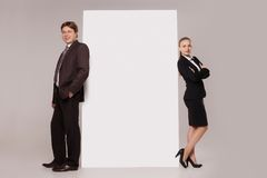 Business man and woman standing over blank banner. Business men and women standing back to back on both sides of blank banner  isolated on grey background Stock Image
