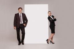 Business man and woman standing over blank banner Stock Photo