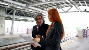 Business man and woman in train station. Business man and woman are talking about their project while waiting for the train