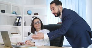 Business man and woman using laptop in office stock video