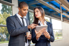 Business man and woman working outdoors with tablet computer in Stock Images