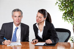 Business man and Woman working Together. A man and woman work together while sitting up to an office table Royalty Free Stock Images