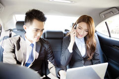 Business man and woman working together in the car Stock Photos