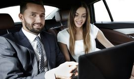 Business man and woman working together in the car. Business people with a laptop working in the back seat of a car Stock Image