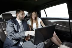 Business man and woman working together in the car Royalty Free Stock Photos