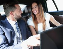 Business man and woman working together in the car. Business people with a laptop working in the back seat of a car Royalty Free Stock Photography