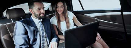 Business man and woman working together in the car. Business people with a laptop working in the back seat of a car Royalty Free Stock Images