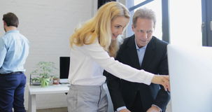 Business man and woman working together with computer in creative office, two professional businesspeople showing on. Monitor discussing data slow motion 60 stock footage