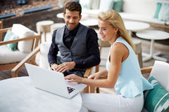 Business man and woman working together on a laptop in modern cafe stock image