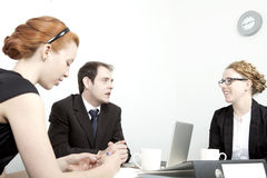 Business man and women having a meeting. Business men and women having a meeting grouped around a table and laptop in an office discussing their plans and Royalty Free Stock Photography