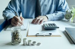 Business man work writing document and putting calculator on tab. Le in office for finance,accounting concept Stock Photography