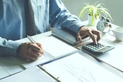 Business man work writing document and putting calculator on tab. Le in office for finance,accounting concept Royalty Free Stock Image