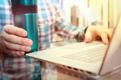Business man working and analyzing financial figures using laptop in the office with cofee or tee Royalty Free Stock Photography