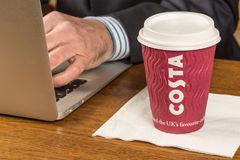Business man working with a Costa coffee next to him stock photos