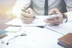 Business man working. Hand  phone  and  pen Stock Images