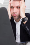 Business man working and having problem with using laptop. Looking at screen and holding his head with both hands, businessman sitting at the desk, computer Royalty Free Stock Photography