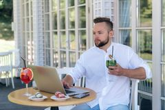 A business man is working on his laptop, waiting for his partners at a table in a cafe, drinking a cold cocktail. Concentrating on the computer monitor Royalty Free Stock Photos