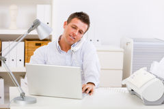 Business man working at home. Business man working on computer at home calling on phone royalty free stock photo