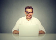 Business man working on laptop computer, smiling Stock Images
