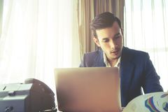 Business man working on laptop on office desk with light shin royalty free stock photo