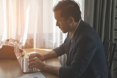 Business man working on laptop on office desk with light shining in Royalty Free Stock Photo