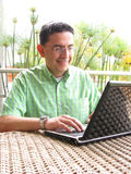Business man working on laptop smiling. Business man working on laptop with glasses Royalty Free Stock Photography