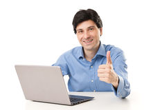 Business man working at the laptop with thumb up gesture Stock Image